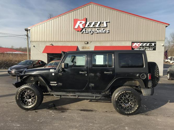 2012 Black /Charcoal Jeep Wrangler Unlimited Sport 4WD (1C4BJWDG1CL) with an 3.6L V6 DOHC 24V FFV engine, Automatic transmission, located at 11115 Chardon Rd. , Chardon, OH, 44024, (440) 214-9705, 41.580246, -81.241943 - Photo #0